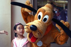 A Chinese girl poses for a photo next to the Disney character Pluto in Shanghai Disneyland, China