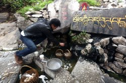 A Chinese tourist grabs a soft-boiled egg at the Mugecuo plateau lake in Ganzi Prefecture