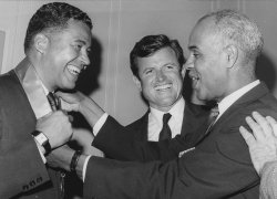 Roy Wilkins shows Sen. Edward M. Kennedy how to place a medal around the neck of Sen. Edward W. Brooke