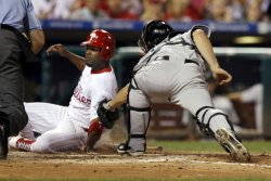 Philadelphia Phillies Jimmy Rollins slides home safe in the third inning.