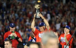 Texas Rangers owner Nolan Ryan holds up the ALCS trophy