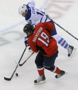 Capitals Backstrom and Maple Leafs Stempniak fight for puck control in Washington