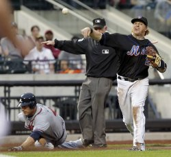 Atlanta Braves Joe Mather slides safe into third while New York Mets Justin Turner throws to first base at Citi Field in New York