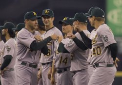 Oakland Athletics pitcher Brett Anderson(left) bumps fists with teammates after being introduced during the Seattle Mariners opening home game