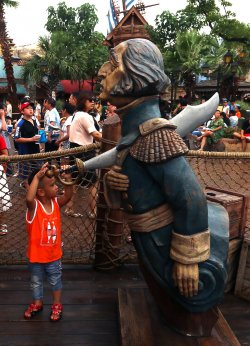 A young Chinese boy inspects a statue in Shanghai Disneyland, China