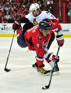 Washington Capitals' Alex Ovechkin fights for the puck against Ottawa Senators' Milan Michalek in Washington