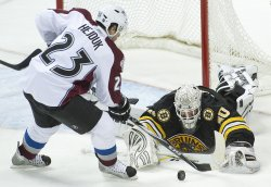 Bruins Goalie Thomas Makes a Save Against the Avalanche's Hejduk in Denver....Flags Fly at Half-Staff Day after Assassination Attempt Against U.S. Rep Giffords in Florence, Arizona