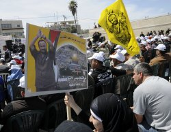 Palestinians hold photos of relatives in Israeli prisons on Palestinian Prisoners' Day in Ramallah