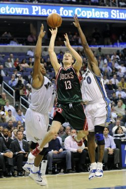 Bucks Ridnour is blocked by Wizards Butler and Arenas in Washington