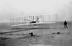 ORVILLE WRIGHT PILOTS THE FIRST FLIGHT
