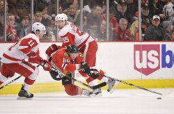 Blackhawks Kopecky reaches for puck against Red Wings in Chicago