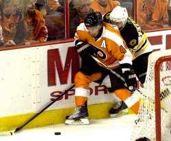 Philadelphia Timonen and Boston's Peverley battle behind the net during first period in Philadelphia.