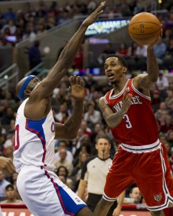 Milwaukee Bucks' Brandon Jennings passes the ball by Los Angeles Clippers' Reggie Evans in Los Angeles