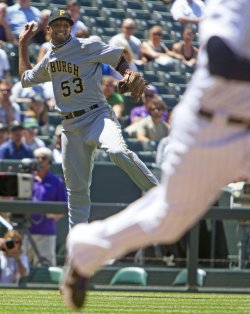 Pirates Pitcher McDonald Leaps for Throw Against the Rockies in Denver