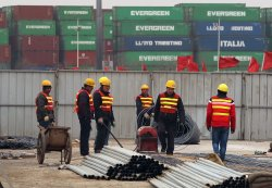 Chinese workers construct a new storage area in Tianjin's port in China