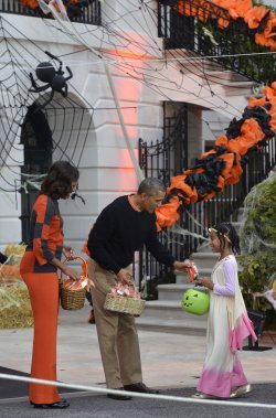 Pres Obama and First Lady Michelle Obama welcome trick-or-treaters to the White House for Halloween