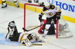 Bruins goalie Tim Thomas falls to the ground as Bruins' David Krejci and Washington Capitals Keith Aucoin run into the goal in Washington