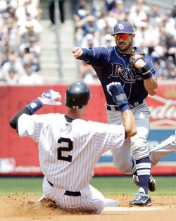 New York Yankees Derek Jeter slides into second base as Tampa Bay Rays Sean Rodriguez throws to first base at Yankee Stadium in New York
