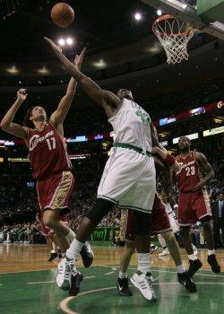 Celtics Perkins and Cavaliers Varejao reach for rebound in Boston, MA.