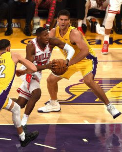 Bulls guard Kris Dunn drives by Lakers center Brook Lopez