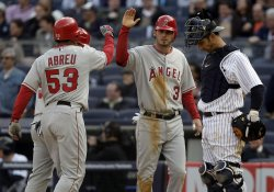 New York Yankees Jorge Posada looks down while Los Angeles Angels of Anaheim Bobby Abreu and Brandon Wood celebrate on opening day at Yankee Stadium in New York