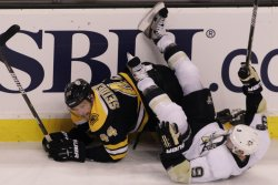 Penguins Dupuis falls on Bruins Seidenberg at TD Garden in Boston, MA.