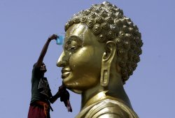 An Indian Buddhist monk cleans the statue of Lord Buddha on the eve of Buddha Purnima in India