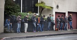 Tech workers wait for a bus in San Francisco