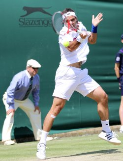 Fernando Gonzalez returns at Wimbledon.