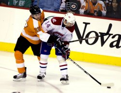 Flyers' Carie and Canadiens Tomas Plekanec try to control the puck in Philadelphia