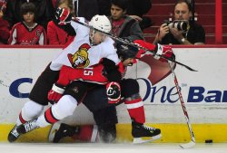 Ottawa Senators' Chris Campoli fights for the puck against Washington Capitals' Boyd Gordon in Washington
