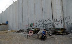A Boy Sits In Front Of Israeli Separation Wall In Abu Dis,West Bank