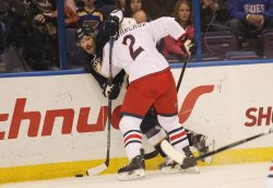 St. Louis Blues Troy Brouwer is pinned against the boards by Columbus Blue Jackets Andrew Bodnarchuk