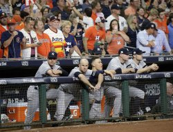 Yankees line up along rail in dugout in the ALCS