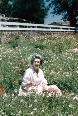 Lady Bird Johnson sits in a patch of wildflowers in front of the LBJ Ranchhouse in Stonewall, TX