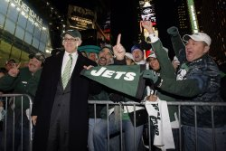 New York Jets owner Woody Johnson takes pictures with Jets fans during a Jets playoff rally at Times Square in New York