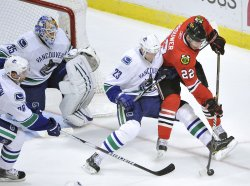 Blackhawks Brouwer and Canucks Edler go for puck in Chicago