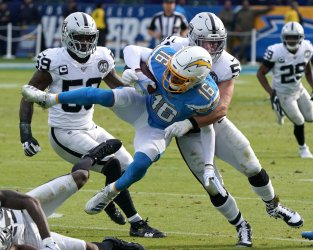 Los Angeles Chargers' receiver Andre Patton is tackled by Oakland Raiders Will Compton