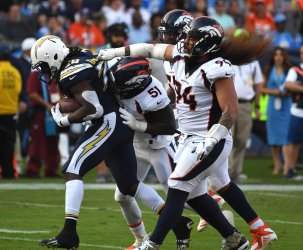 Chargers' running back Melvin Gordon III is tackled by Broncos Todd Davis (51) and Domata Peko Sr (94)