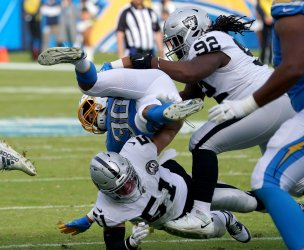 Los Angeles Chargers' running back Austin Ekeler (30) is upended by  Oakland Raiders Will Compton