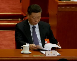 Xi reads a government report at the opening of the NPC in Beijing, China