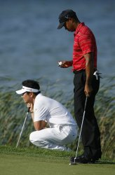 Tiger Woods and Y. E. Yang line up their putts on the 16th hole during the final round of the 91st PGA Championship in Chaska, Minnesota
