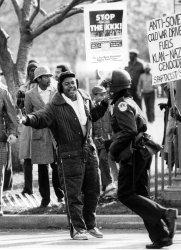 One of several hundred anti-Ku Klux Klan demonstrators jeers as a policeman runs by