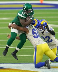 New York Jets running back Frank Gore is tackled in air by Los Angeles Rams Justin Hollins  in Inglewood