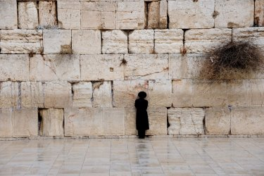 An Ultra-Orthodox Israeli prays after a rain storm at the Western Wall in Jerusalem's Old City