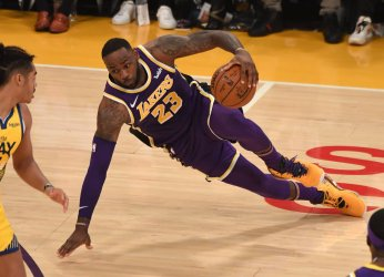 Lakers forward LeBron James continues his dribble while falling to the court against the Warriors at Staples Center
