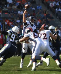Broncos' quarterback Case Keenum throws a pass against the  Chargers' Tackle Corey Luget