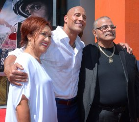 Dwayne Johnson places hands and footprints in wet cement at TCL Chinese Theatre in Los Angeles