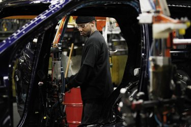 Worker installs door on car at Ford plant in Chicago