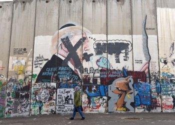 A Palestinian Walk Past Graffiti Of U.S. President Donald Trump In Bethlehem